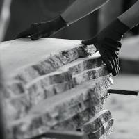 gloved hands pull natural edge boards off the bandsaw rollers and onto the stack