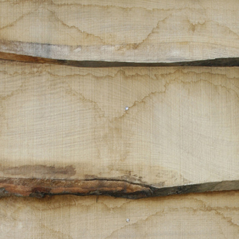 a detail of waney edge oak cladding with water markes showing movement of tannin in the timber surface