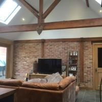 the-green-oak-building-company-oak-framed-interior-with-exposed-roof-structure-red-brick-infill-panels-and-oak-joinery